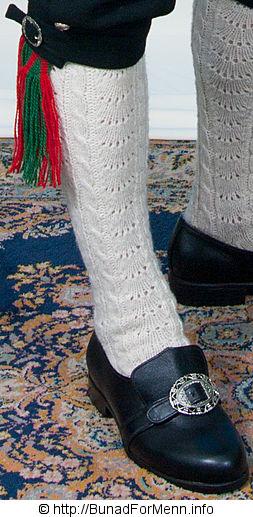 Strømper og hosebånd er håndlagde i norsk ull av aller beste kvalitet. Strømpene er strikket i ubleket garn med et tradisjonelt flettemønster.