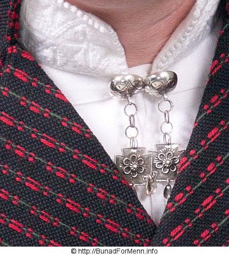 Alt vårt sølv er laget i vår egen sølvsmie av sølvsmeder med høy fagkompetanse. Bunad For Menn vektlegger også her kvalitet og håndverkstradisjon av aller ypperste klasse. Sølvnålen i halsen på skjorten til Vest-Agder bunaden lages som et klassisk anheng med Gotiske kors.