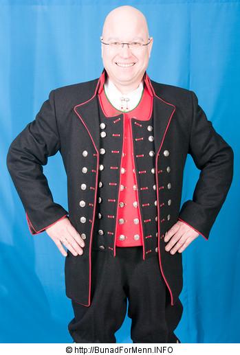Mannsbunad fra Fana med rød vest, svart jakke uten armer, frakk og knebukse. Bunaden bærer tydelig preg av å være en tidligere orlogs uniform.