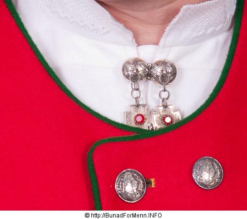 Sølvnålen i halsen på skjorten til Fanabunaden lages som et klassisk anheng med Gotiske kors dekorert med en rød sten. Mansjettknappene er i likhet med knappene på jakke, bukse og vesten, dekorert med Fembladsrosa som fra gammelt av også ble kalt «Bergensølv»