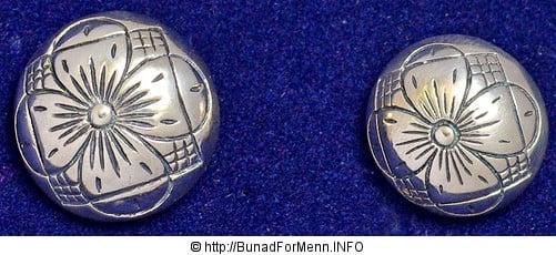 Vi lager knappene i et tradisjonelt Femblads-rose mønster, som er det mest brukte mønsteret i sølvet til denne bunaden. Vesten har ti sølvknapper med klassisk femblads rose mønster.