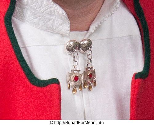 Sølvnålen i halsen på skjorten til bunaden lages som et klassisk anheng med Gotiske kors.