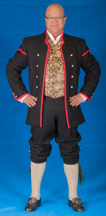 Den lange jakken til Gudbrandsdalbunaden er laget i svart eller hvit Engelsk klede, et ullstoff vevet som såkalt toskafta materiale av ren ull, med innblanding av Merinoull.