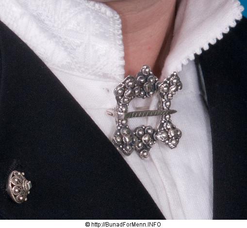 Halsnålen som på folkemunne er kalt Hornring er laget for hånd i klassisk filigran stil. Dette er en halsnål haåndlaget i sølv av våre dyktige sølvsmeder.