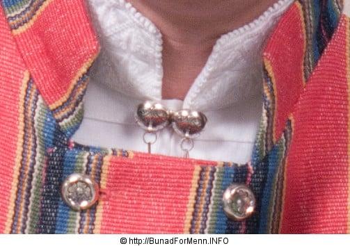 Sølvnålen i halsen på skjorten til Trønderbunadene er laget som et klassisk anheng med Gotiske kors. Mansjettknappene er dekorert med fembladsrosa som fra gammelt av også ble kalt «Bergensølv» Grunnen til dette var at Bergen var kjent for sin produksjon av kvalitetsølv.
