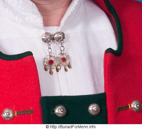 Sølvnål du bærer i halsen. Nålen har gotiske kors.