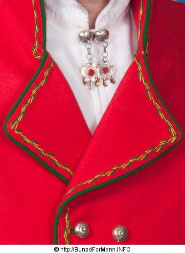 Den lange jakken er prydet med broderier og grønne biser, slik det er vist på bildet på vår nettside.