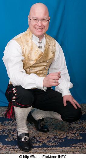 Jakken er laget i svart drapé med silke i forskjellige farger og mønster på jakkeslaget, slik det er vist på bildet på vår nettside. Bunad For Menn har lagt vekt på både kvalitet og etnisitet når de har valgt ut leverandører av materialet til sine bunader. Jakken har svart silkefor innvendig
