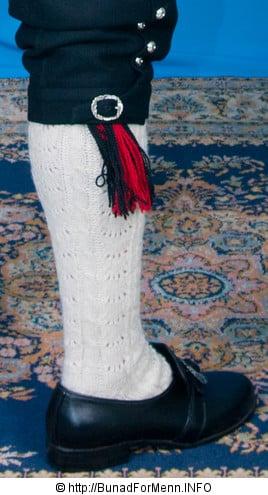 Strømper og hosebånd til mannsbunad fra Sogn med rød jakke er håndlagde i norsk ull av aller beste kvalitet. Strømpene er strikket i ubleket garn med et tradisjonelt flettemønster.