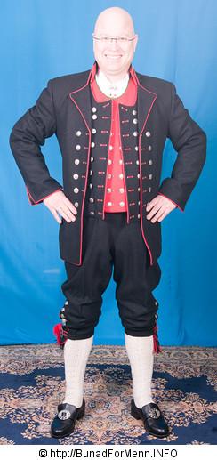 Den lange jakken er kantet med røde biser slik det er vist på bildet på vår nettside.