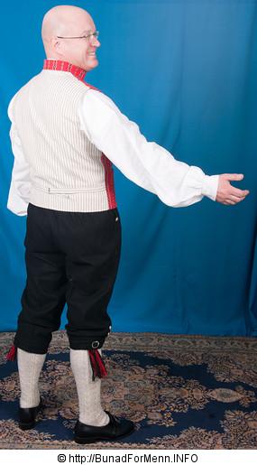 Ryggen på vesten er laget av håndvevet stripet lerretstoff til herrebunad fra Østfold.  Vi har valgt å bruke dette materialet i ryggen på vesten da lerret ikke blir skrukkete når man har på seg jakken, i motsetning til Baskerlin som er den billige varianten av materiale til bruk i ryggen på vesten. Bunad For Menn er stolte av å ha tatt i bruk det stripede håndvevete bomullsstoffet i ryggen på sin ullvest fra Østfold. Silken til silkebrokade vesten er kjøpt inn fra små veverier i Mekongdalen. Dette er silke av beste kvalitet med mønsteret som har lang tradisjon tilbake i tid og fortsatt er i bruk i Østfold.