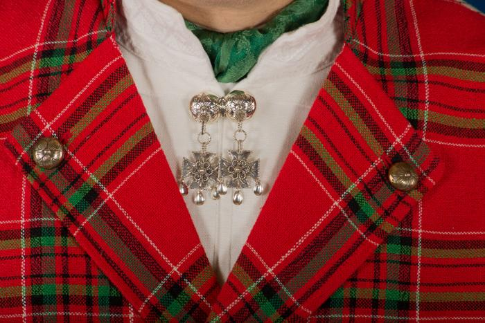 Sølvnålen i halsen på skjorten til Gudbrandsdalbunaden lages som et klassisk anheng med Gotiske kors. Mansjettknappene er i likhet med knappene på jakke, bukse og vesten dekorert med Fembladsrosa som fra gammelt av også ble kalt «Bergensølv».