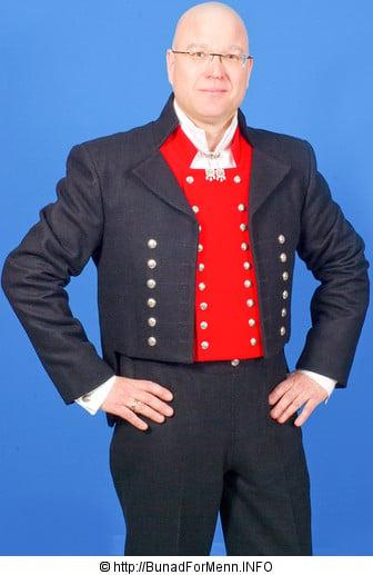 Mannsbunad fra Nordmøre med svart jakke i Engelsk klede. Jakken er foret med silke og er en klassisk kort jakke. Knappene på jakken er i sølv med klasisk mønster av femblads rosa og håndbroderte knappehull. Bunaden er utstyrt med kort bukse i svart klede med lokk foran og sølv knapper og spenne. Jakke og bukse er laget i Engelsk klede som er et 100% materiale av ull med innblandet Merinoull som gir kleden en svært høy kvalitet.