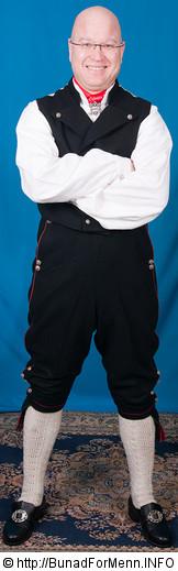 Buksen til mannsbunad fra Øst-Telemark med hvit jakkeer laget av svart klede med røde og grønne biser. Her er det brukt klede av aller beste kvalitet. Bunad For Menn lager både nikkers og lang bukse til bunaden.