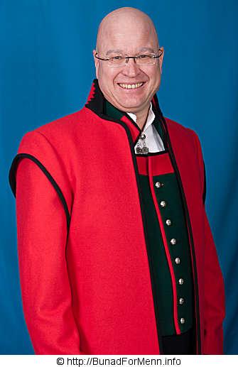 Mannsbunad fra Sogn med rød jakke i Engelsk klede med svarte biser. Jakken er uten knapper og fôret med silke innvendig. Jakken lages også i mørk rød farge med svarte biser.