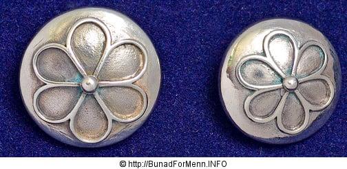 Mansjettknappene er i likhet med knappene på jakke, bukse og vesten i sølv. Mansjettknappene er laget i samme Femblads rosemønster mønster som knappene.