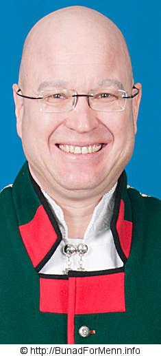 Sølvnål til halsen med gotisk kors til mannsbunad fra Sogn med rød jakke.