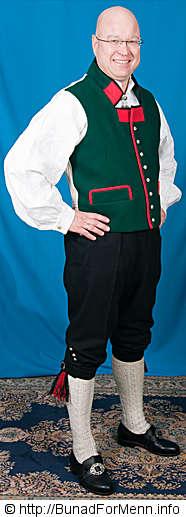 Bunaden er utstyrt med kort bukse i svart klede med lokk foran og sølv knapper og spenne. Buksen til mannsbunad fra Sogn med rød jakke er laget av svart Engelsk klede.