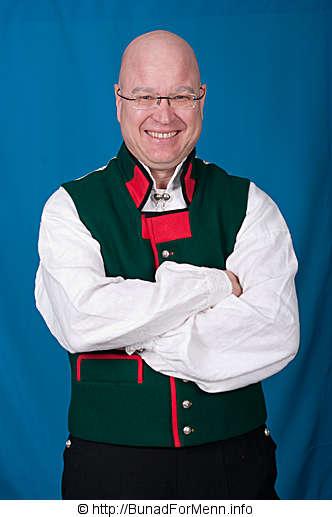 Den grønne vesten er utstyrt med rød bise i front og rød bise på lommeklaffene som vender oppover. Vesten har ti sølvknapper med klassisk femblads rose mønster.