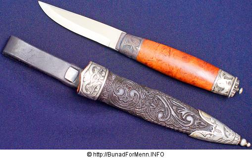 Som ekstra tilbehør til mannsbunad fra Øst-Telemark med hvit jakke anbefaler vi en bunadskniv. BFM lager en eksklusiv kniv med håndsmidd blad. Kniven har håndsmidd blad og håndsydd slire. Både sliren og kniven har sølvbeslag.