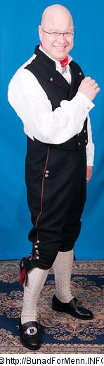 Buksen til Øst-Telemark bunaden er laget av svart klede med røde og grønne biser. Her er det brukt klede av aller beste kvalitet. Bunad For Menn lager både nikkers og lang bukse til bunaden.