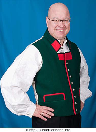 Grønn vest med rød krage og gult sikksakk mønster til mannsbunad fra Sogn med rød jakke.